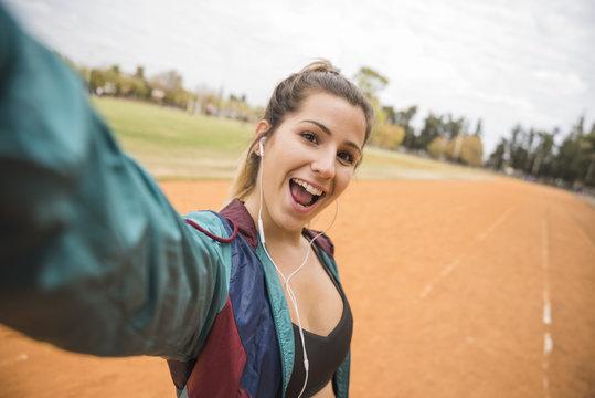 Sporty woman taking selfie on stadium track