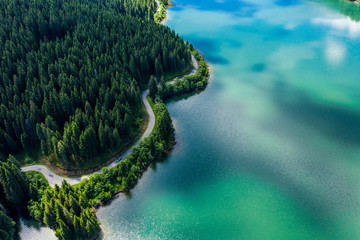 Aerial view over beautiful turquoise mountain lake and green forest. Spring in the mountains. Green forest, mountain lake. Green pine and fir trees forest and a lake. Beautiful mountain road. - Image