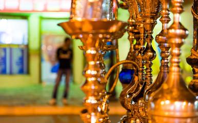 shiny beautiful hookahs on market shelfs under night arabian city lights
