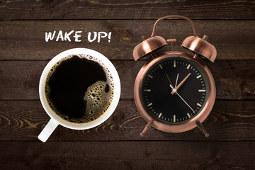 Mug of coffee and classical copper colored alarm clock with bells in a Wake Up concept on a wooden...