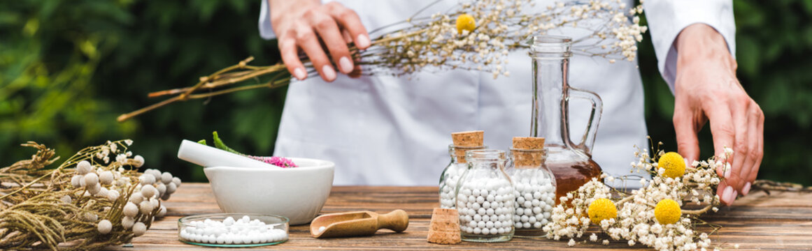panoramic shot of woman holding gypsophila flowers near bottles with pills