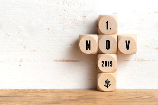 1st November date on wooden blocks formed as a cross on a table with copy space on a wall All Saints Day in Catholicism