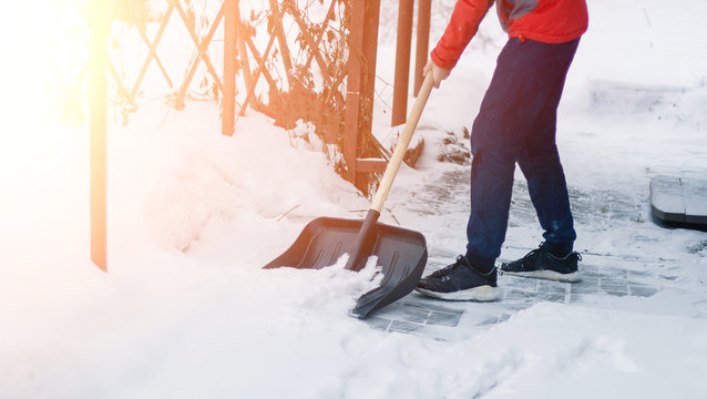 A man cleans up, cleans snow from the sidewalk after a blizzard, snowfall. a civil servant in a snowfall with one shovel in a winter blizzard. leaning a shovel on the snow on the driveway. drifts.