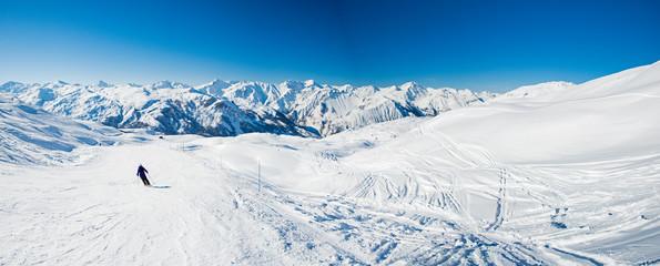 Skiers on a piste in alpine ski resort Fototapete