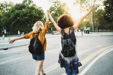 Tuinposter Milan Couple of young women from the back holding hands with arms raised and they walk in the street at sunset - Two millennials are happy