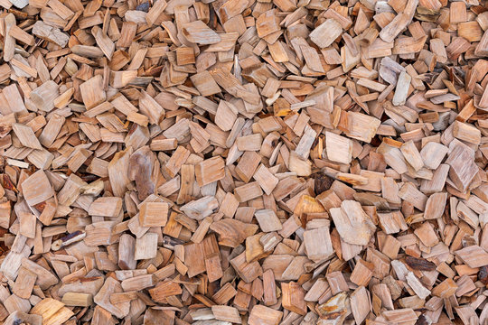 A pile of wood sawdust lies on the ground, background