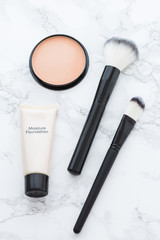 Tube of concealer, powder and brushes