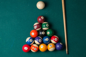 Old billiard balls and stick on a green table. billiard balls isolated on a green background.