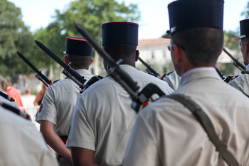 French soldiers and police standing still during the Bastille celebration in Nimes, France