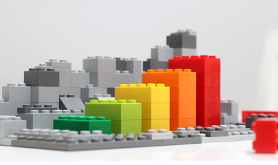 Progress chart made of brick toys. Isometric composition of colourful toys on white table.