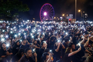 Demonstrators wave their smartphones during a rally ahead of the G20 summit, urging the international community to back their demands for the government to withdraw a the extradition bill in Hong Kong