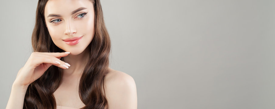 Closeup portrait of beautiful woman with clear skin smiling and looking aside on gray banner background