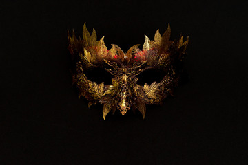 Cosplay, Venetian mask in gold and red with metallic pieces in the form of leaves. original and unique design, handmade crafts