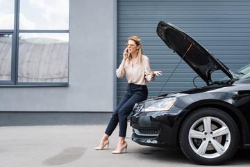 beautiful businesswoman talking on smartphone near broken auto, car insurance concept