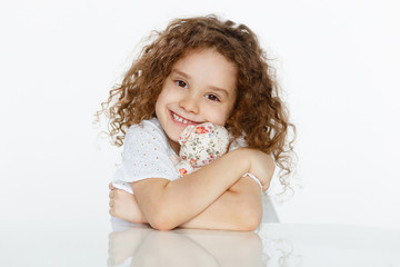 Frontal portrait of cheerful cute curly little girl embracing a toy, seated at table over white background. Copy space.