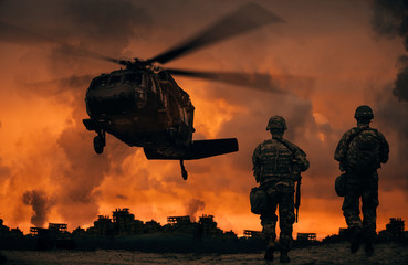 Military soldiers walking to helicopter in battlefield at sunset Wall mural