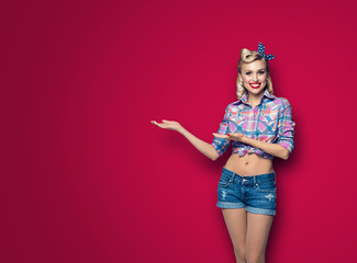Photo of woman in pin up style, showing something or copyspace, over dark red background Fototapete