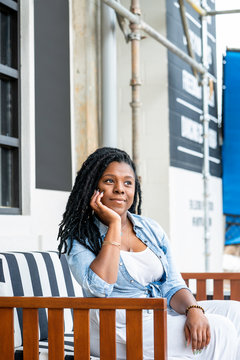 Woman with dreadlocks sitting on outdoor sofa