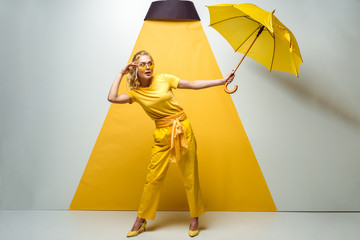 attractive blonde girl touching sunglasses and holding umbrella on white and yellow Wall mural