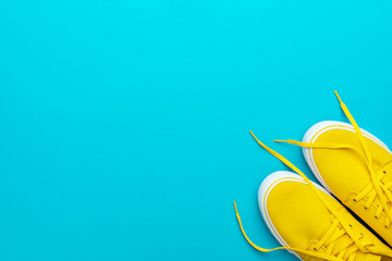 Flat lay image of yellow summer footwear. Pair of yellow sneakers on turquoise blue background. Top view of skateboarding shoes with copy space. Minimalist photo of sneakers with untied shoelaces