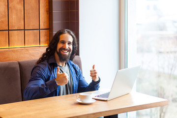 Portrait of positive handsome intelligence young adult man freelancer in casual style sitting in cafe with laptop, showing thumbs up and toothy smile, looking at camera. Indoor, lifestyle concept