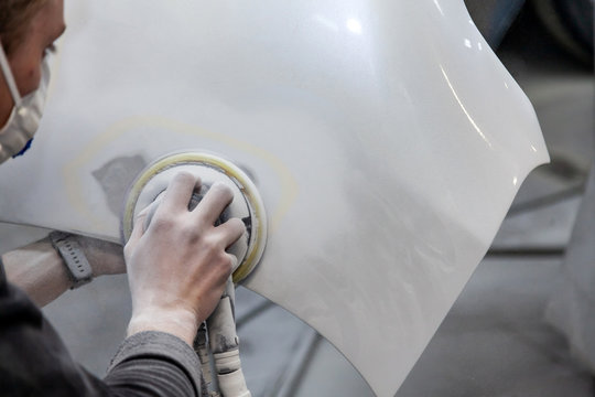 Preparation for painting a car element using sander and putty by a service technician leveling out before applying a primer after damage to a part of the body in an accident in the vehicle workshop