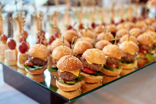 Buffet table with mini hamburgers and canape at luxury wedding reception, copy space. Serving food and appetizers at restaurant. Catering banquet table