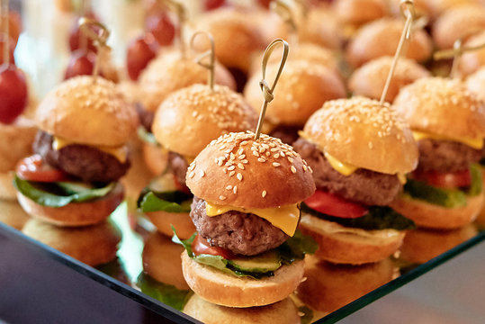 Buffet table with mini hamburgers at luxury wedding reception, copy space. Serving food and appetizers at restaurant. Catering banquet table