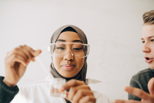 Teenage boy talking to female classmate during experiment in science class
