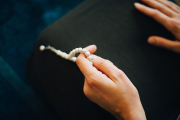 Cropped image of woman praying with rosary beads at home