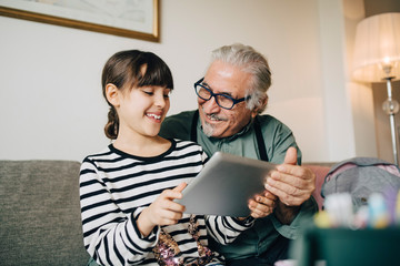 Smiling grandfather and granddaughter looking at digital tablet while sitting in living room at home
