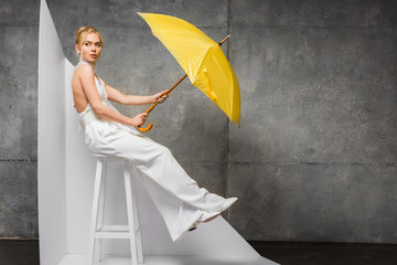 attractive blonde woman sitting on chair and holding yellow umbrella on white and grey