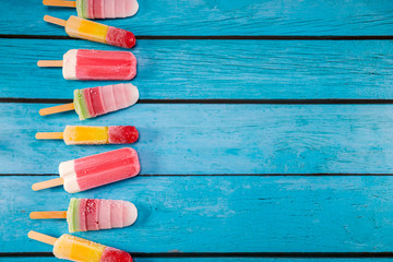 Colorful fruit ice cream stick look fresh to eat placed on a blue vintage