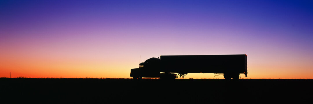 Silhouette of semi-truck against dramatic sky