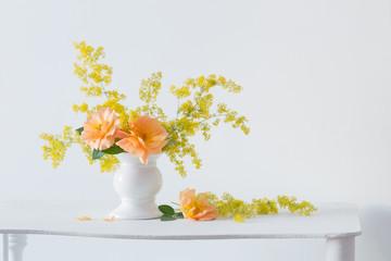 orange roses with wild flowers in bouquet in white vase in interior