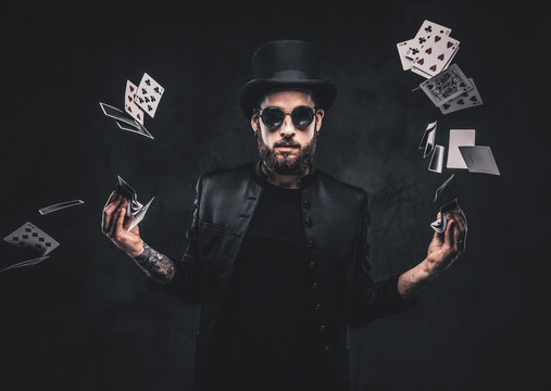 Magician in a black suit, sunglasses and top hat, showing trick with playing cards on a dark background.