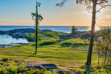 Sunrise of a classic midsommer pole at the green coast of Roslagen