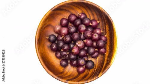 Fototapete Put grapes into wooden plate on white background, Stop Motion