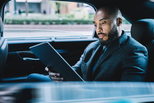 Businessman with black skin sitting on backseat in taxi automobile and searching contact number for making online video conference via modern touch pad, concept of market digitalisation on tablet