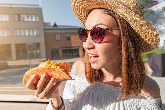 Happy asian girl eating taco outside. Mexican fastfood cuisine. Tasty and spicy snack in park