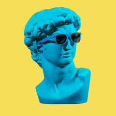Statue. Earphone. Isolated. Gypsum statue of David's head. Man. Creative. Plaster statue of David's head in blue sunglasses. Minimal concept art.