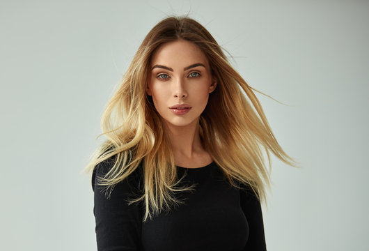 Portrait of blonde woman with blowing hair looking at camera and isolated on gray background