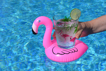 Woman holding a drink in a pink flamingo inflatable drinks holder in a swimming poo.