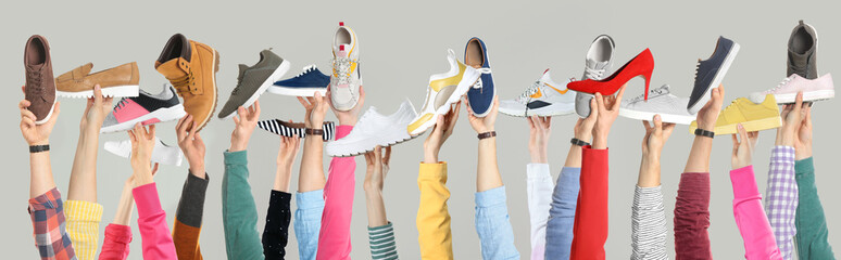 Wall Mural - Set of people holding different stylish shoes on color background, closeup