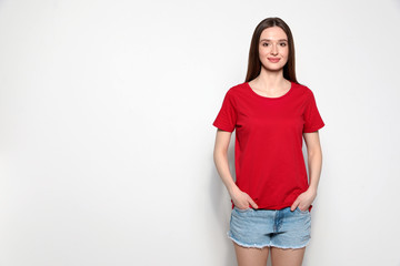 Wall Mural - Young woman in t-shirt on light background. Mock up for design