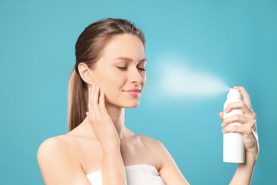 Young woman applying thermal water on face against color background. Cosmetic product