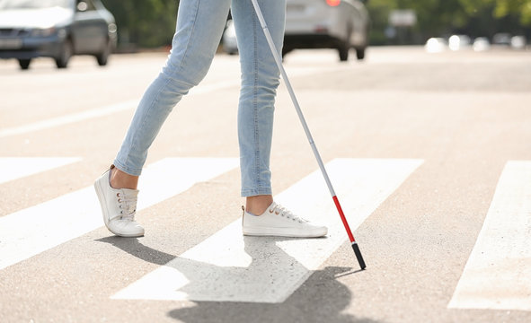 Blind person with long cane crossing road, closeup