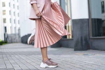 Pleated skirt coral color and sneakers. The girl is very dynamic posing on the street, the skirt is developing. Wall mural
