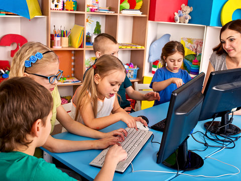 Computer education for children use computer game in class with teacher.