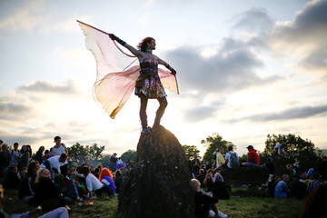 A festival goer dances during sunset at the stone circle during Glastonbury Festival at Worthy farm in Somerset